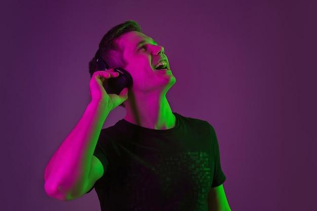 Portret van de jonge man geïsoleerd op paarse studiomuur in neonlicht