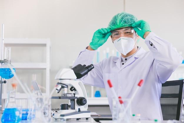 Portret van de jonge mannelijke wetenschapper van azië die gezichtsmasker en veiligheidsbril met materiaal in een laboratorium draagt.