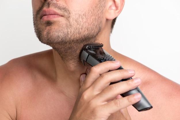 Portret van de jonge mens die zijn baard met elektrisch scheerapparaat scheert