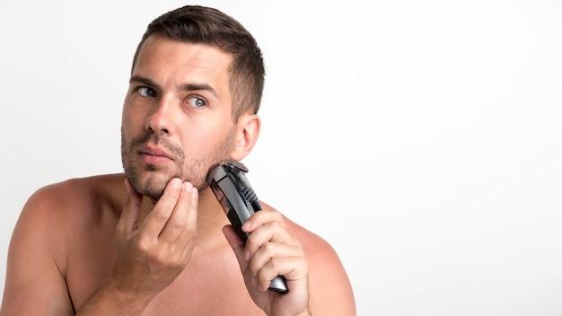 Portret van de jonge mens die zijn baard met snoeischaar in orde maakt