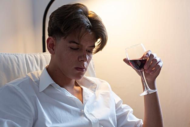 Portret van de jonge mens in wit overhemd het drinken wijn thuis