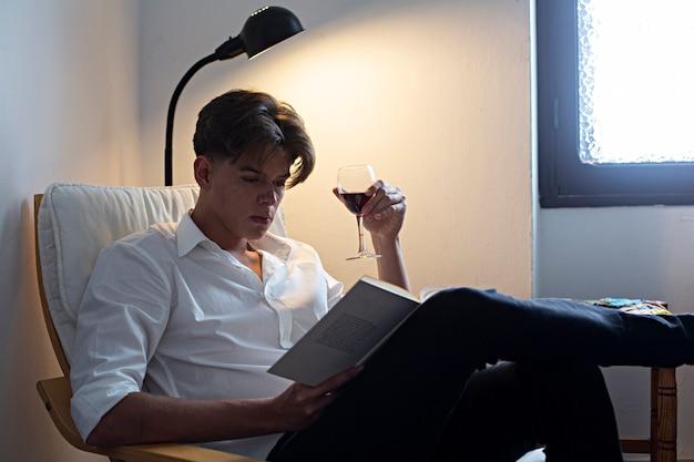 Portret van de jonge mens in witte overhemdszitting het drinken wijn en thuis het lezen van een boek