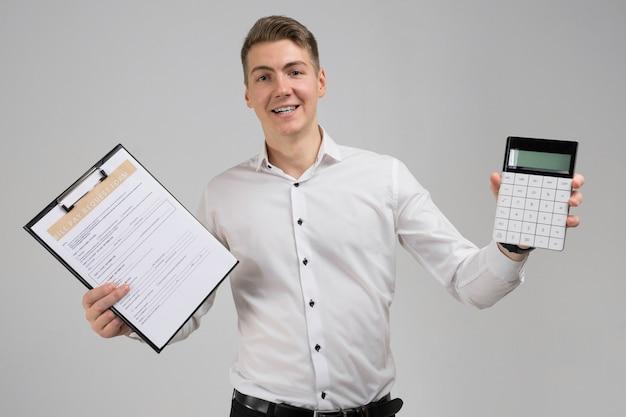 Portret van de jonge mens met geïsoleerde vorm van betaling van rekeningen en calculator in zijn handen