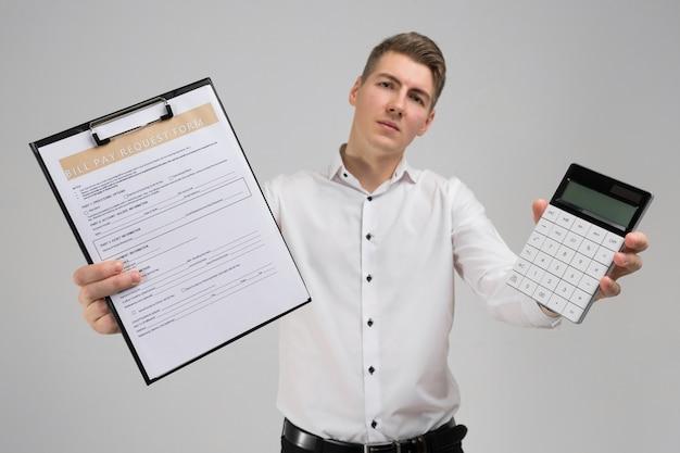 Portret van de jonge mens met vorm van betaling van rekeningen en calculator in zijn die handen op wit wordt geïsoleerd