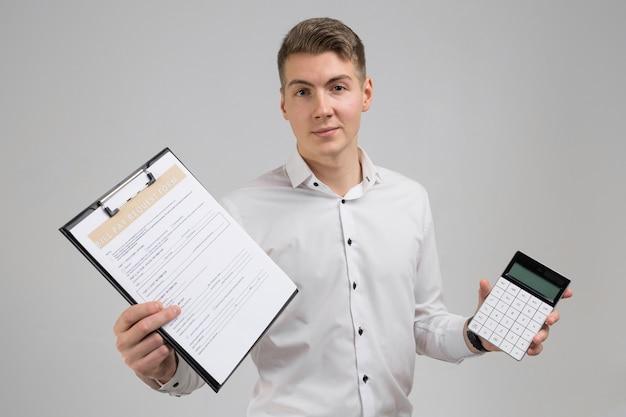 Portret van de jonge mens met vorm van betaling van rekeningen en calculator in zijn die handen op witte t-shirt wordt geïsoleerd