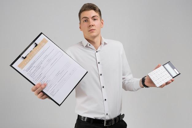 Portret van de jonge mens met vorm van betaling van rekeningen en calculator in zijn handen op wit