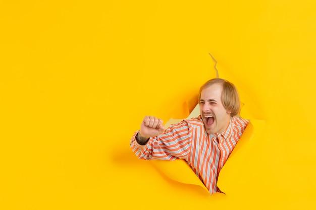 Portret van de jonge mens op gele gescheurde doorbraakachtergrond