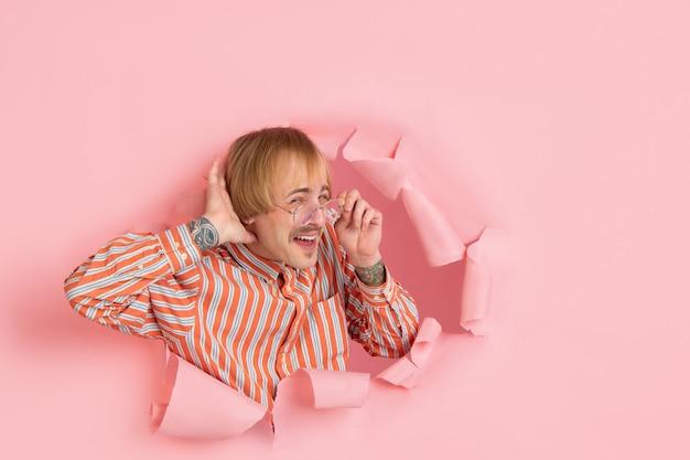 Portret van de jonge mens op roze gescheurde doorbraakachtergrond
