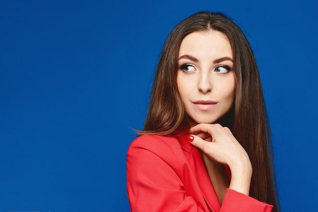 Portret van de jonge modelvrouw met perfecte naaktmake-up in een rood kostuum tegen het blauwe oppervlak