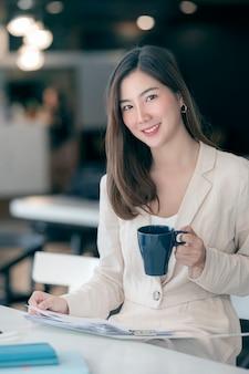 Portret van de jonge mooie aziatische mok en het papierwerk van de vrouwenholding zittend op kantoor