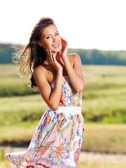 Portret van de jonge mooie glimlachende vrouw buitenshuis