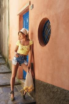 Portret van de jonge mooie netto zak van de vrouwenholding met heel wat verse citroenen