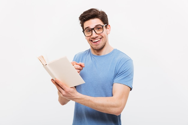 Portret van de jonge slimme mens in blauw overhemd die oogglazen dragen die terwijl het lezen van prettige informatie glimlachen, over witte muur wordt geïsoleerd