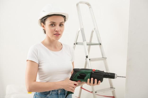Portret van de jonge vrouw inhoud in veiligheidshelm met behulp van elektrische boor tijdens renovatie in nieuwe flat