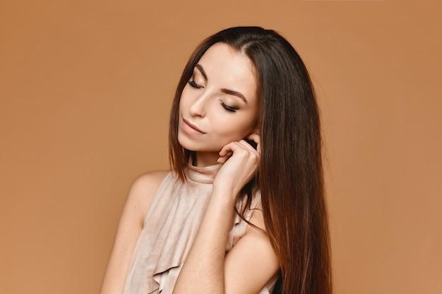 Portret van de jonge vrouw met perfecte trendy make-up in een elegante beige jurk poseren in studio op het beige oppervlak concept van modieuze avondmake-up en gladde huid
