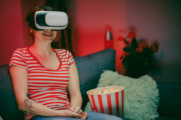 Portret van de jonge vrouw op de bank zitten en de vr-headset hebben, iets kijken terwijl ze popcorn eten en glimlachen