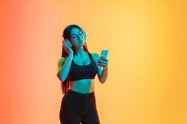 Portret van de jonge vrouw op geeloranje in neonlicht