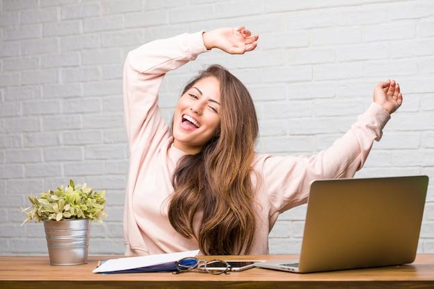 Portret van de jonge zitting van de studenten latijnse vrouw op haar bureau die aan muziek luisteren