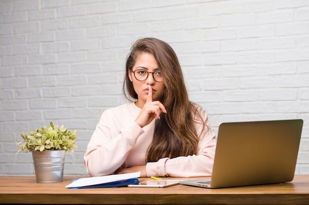 Portret van de jonge zitting van de studenten latijnse vrouw op haar bureau die een geheim houden of om stilte vragen