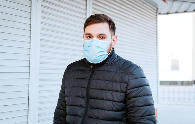 Portret van de kaukasische mens die medisch beschermend masker in openlucht draagt. virus, coronavirusbescherming, luchtverontreiniging, ecologie, milieubewustzijn