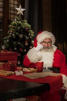 Portret van de kerstman aan de tafel
