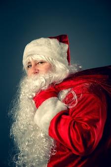 Portret van de kerstman. de kerstman draagt een tas met cadeautjes. kerst fantasie.