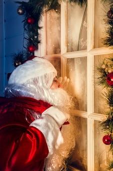 Portret van de kerstman. de kerstman kijkt uit het raam