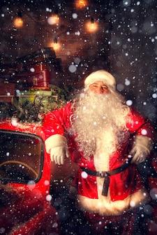 Portret van de kerstman. de kerstman staat met cadeautjes bij de auto