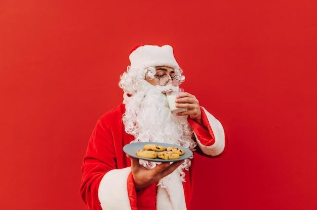 Portret van de kerstman die zich voor een rode muur bevindt
