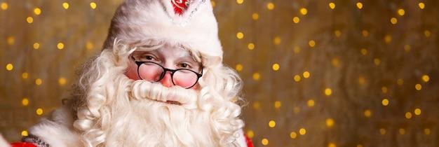 Portret van de kerstman in glazen camera kijken tegen de achtergrond van een muur met bokeh close-up...