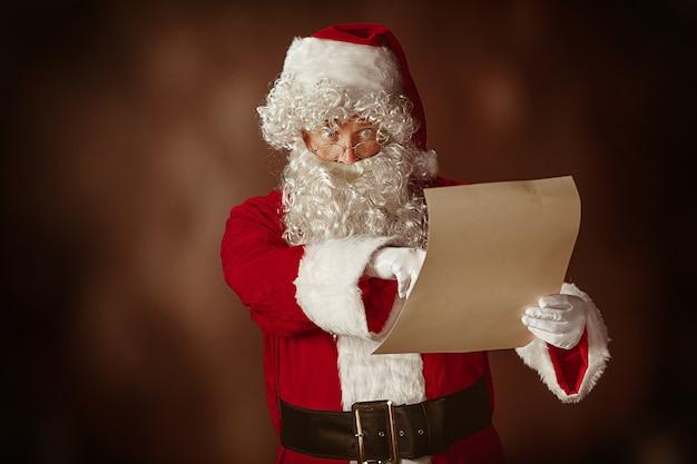 Portret van de kerstman in rood kostuum die een brief lezen