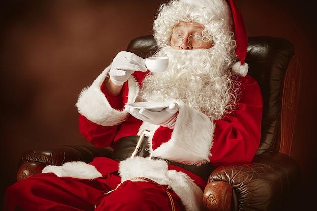 Portret van de kerstman in rood kostuum met koffiekopje