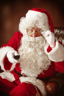 Portret van de kerstman in rood kostuum met tv-afstandsbediening