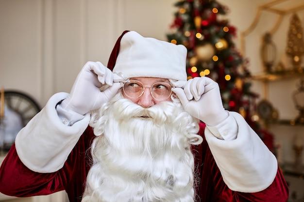 Portret van de kerstman met een bril bij de open haard en de kerstboom met geschenken. vrolijk kerstfeest, prettige feestdagen concept