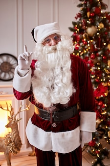 Portret van de kerstman met een bril bij de open haard en de kerstboom met geschenken.