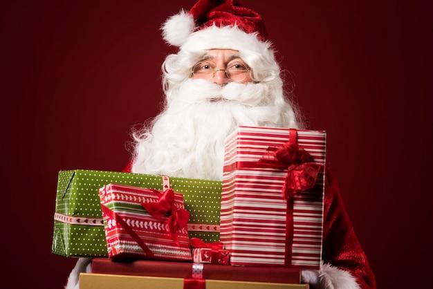 Portret van de kerstman met geschenkdozen op rode achtergrond