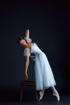 Portret van de klassieke ballerina in witte jurk op zwart