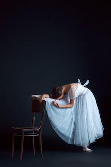 Portret van de klassieke ballerina in witte jurk op zwarte kamer