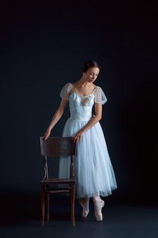 Portret van de klassieke ballerina in witte jurk op zwarte ruimte