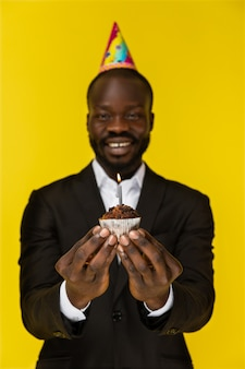 Portret van de knappe afrikaanse mens die een cake met een nadruk op de cake houdt