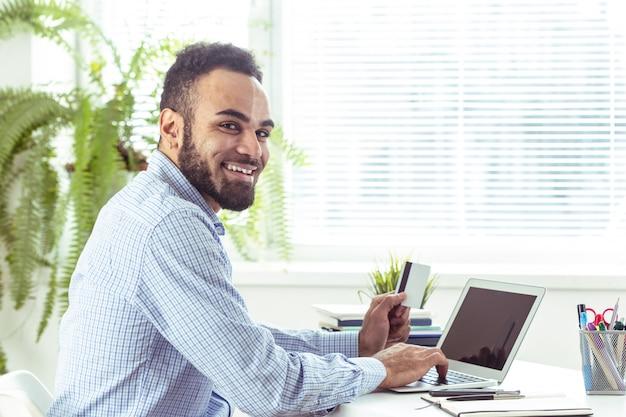 Portret van de knappe afrikaanse zwarte jonge bedrijfsmens die aan laptop op kantoor werken