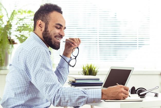 Portret van de knappe afrikaanse zwarte jonge bedrijfsmens die aan laptop op kantoor werkt