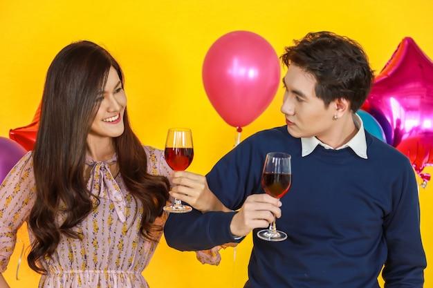 Portret van de knappe aziatische man en mooie vrouw die aan oog kijken en rode wijnglas houden met gele achtergrond en kleurrijke partijballon.