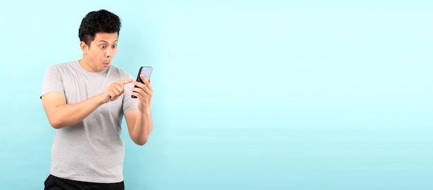 Portret van de knappe aziatische mens die schok en verrast na het lezen van bericht van smarrtphone is, dat op blauwe muur wordt geïsoleerd.
