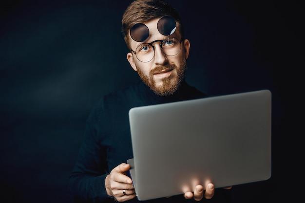 Portret van de knappe donkerbruine gebaarde mens die in bureau werkt dat zilveren laptop met behulp van die over donkere muur wordt geïsoleerd