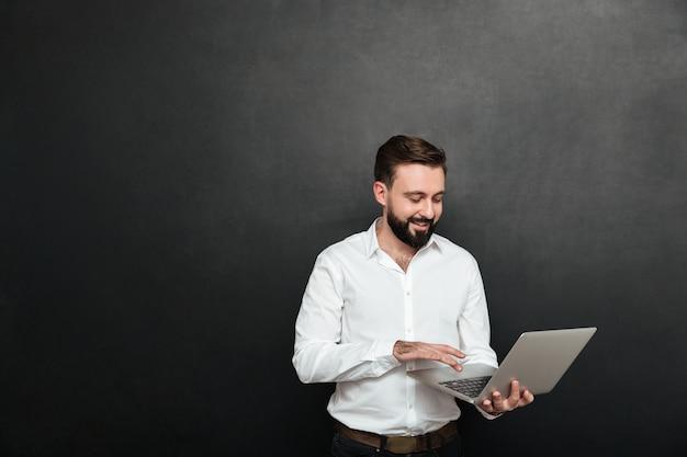 Portret van de knappe donkerbruine mens die in bureau werkt dat zilveren laptop met behulp van, dat over donkergrijze muur wordt geïsoleerd