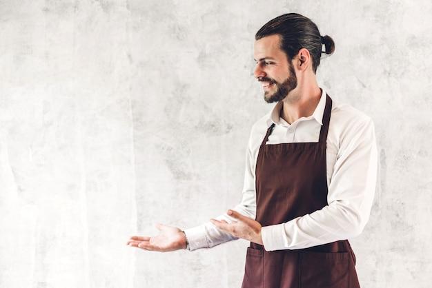 Portret van de knappe gebaarde kleine bedrijfseigenaar die van de baristamens op muurachtergrond glimlachen