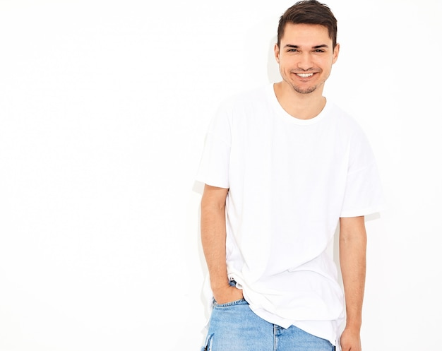 Portret van de knappe glimlachende jonge modelmens gekleed in jeanskleren en t-shirt het stellen. zijn hoofd aanraken