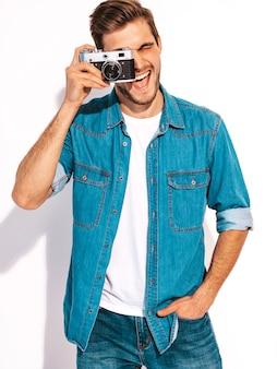Portret van de knappe glimlachende mens die de kleren van de zomerjeans draagt. model mannetje dat beeld op oude uitstekende fotocamera neemt.