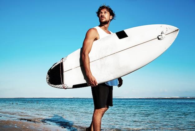 Portret van de knappe hipster zonnebaadde modelsurfer die van de maniermens vrijetijdskleding dragen die met surfplank op blauwe oceaan en hemel gaan